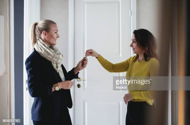 smiling businesswoman giving key to colleague at home - giving stock photos and pictures