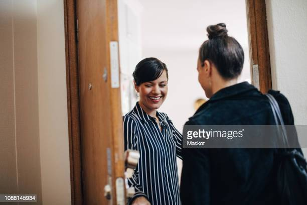 smiling businesswoman greeting colleague while standing at doorway - bezoek stockfoto's en -beelden