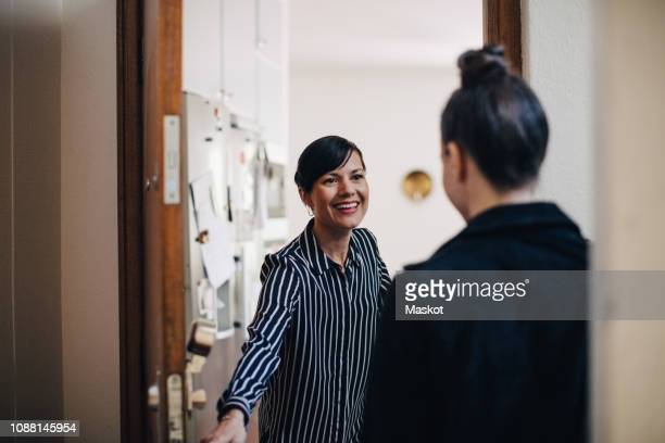 smiling businesswoman greeting coworker at doorway - begroeten stockfoto's en -beelden