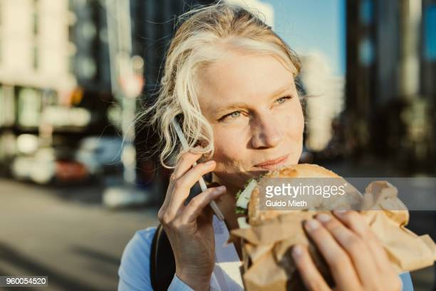 Smiling businesswoman having breakfast while phoning.