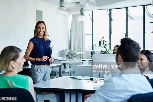 smiling businesswoman having discussion with team - top vergadering stockfoto's en -beelden