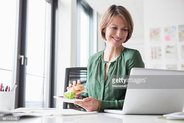 Smiling businesswoman having lunch break at office desk