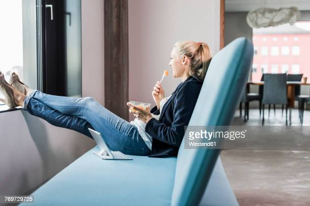 smiling businesswoman having lunch break - comfortabel stockfoto's en -beelden