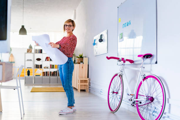 Smiling businesswoman holding blueprint in office