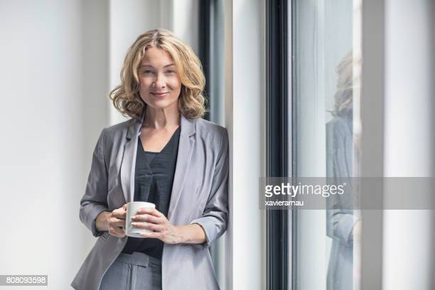 smiling businesswoman holding coffee mug by window - blazer jacket stock photos and pictures