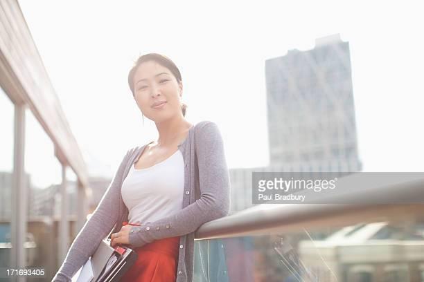 lächelnd geschäftsfrau holding ordner und schiefer - koreanischer abstammung stock-fotos und bilder
