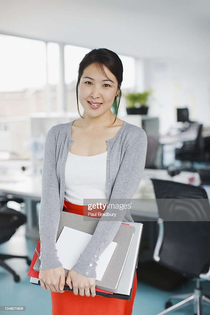 Smiling businesswoman holding laptop and folders in office : Stock Photo