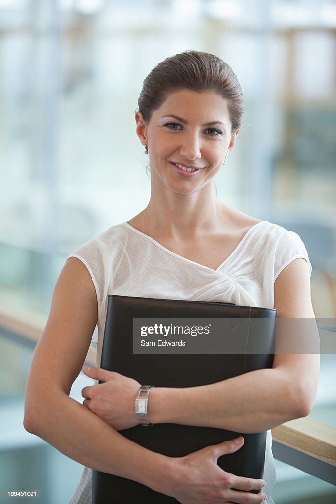 Smiling businesswoman holding paperwork and cell phone : Stock Photo