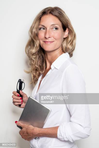 smiling businesswoman holding tablet and glasses - chemisier blanc photos et images de collection