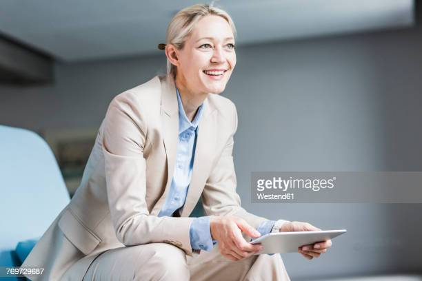 Smiling businesswoman holding tablet