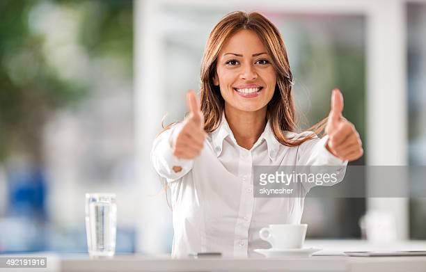 Sorridente Mulher de negócios em um café mostrando os polegares para cima.