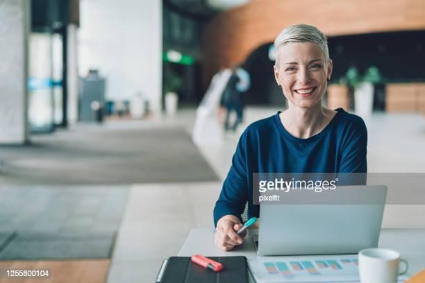 glimlachende onderneemster in een bureaugebouwlobby - onafhankelijkheid stockfoto's en -beelden