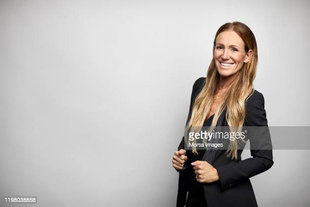 smiling businesswoman in black business casual - dreiviertelansicht stock-fotos und bilder
