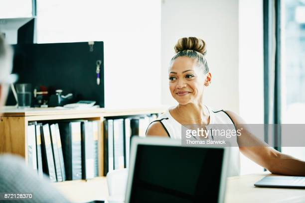 smiling businesswoman in client meeting in office conference room - pacific islanders stock pictures, royalty-free photos & images