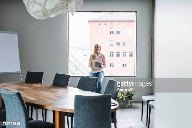 Smiling businesswoman in conference room at the window