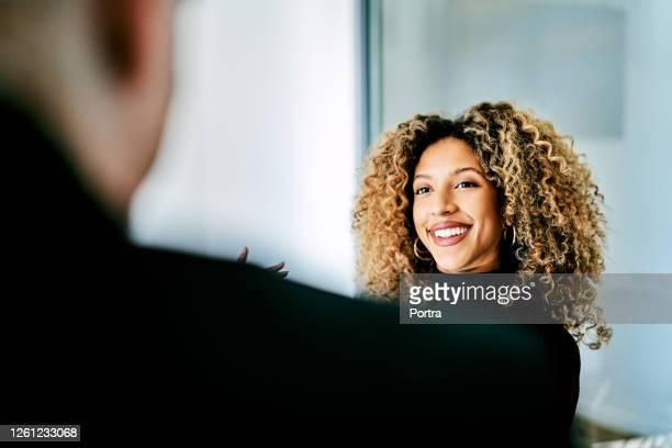 クリエイティブオフィスで笑顔のビジネスウーマン - コイリーヘア ストックフォトと画像