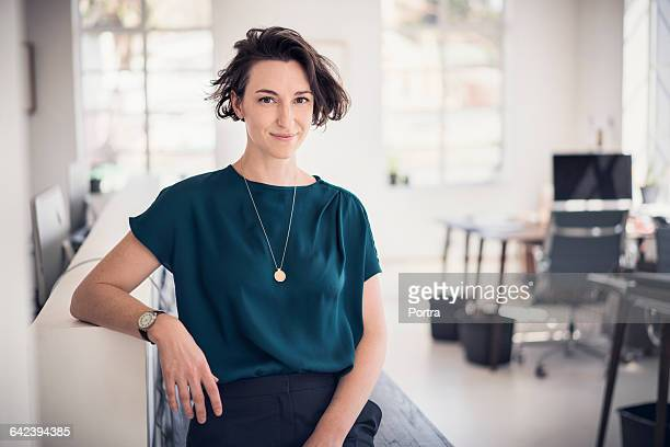 smiling businesswoman in creative office - leanincollection stock pictures, royalty-free photos & images