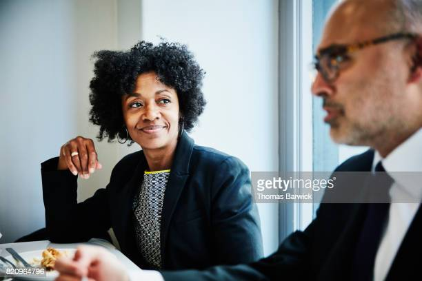 Smiling businesswoman in discussion with colleague during lunch