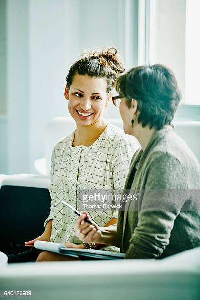 Smiling businesswoman in discussion with colleague