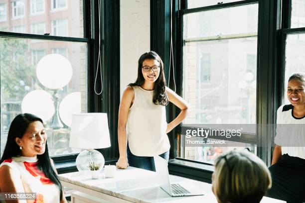 Smiling businesswoman in discussion with coworkers during informal meeting in office