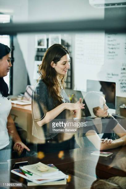 smiling businesswoman in discussion with coworkers during meeting in design studio - agence de design photos et images de collection