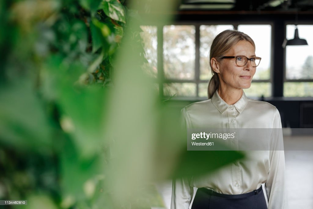 Smiling businesswoman in green office : Stock-Foto