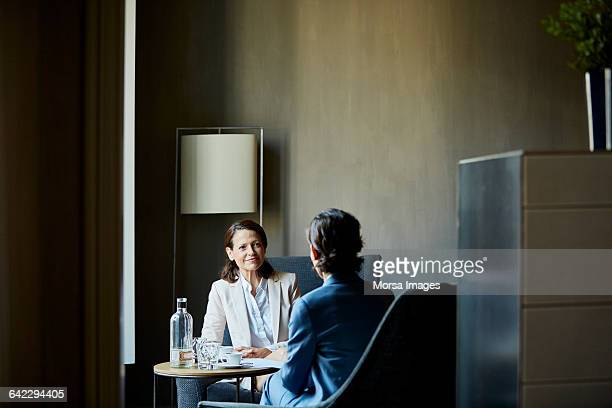 smiling businesswoman in meeting at hotel room - leanincollection stock pictures, royalty-free photos & images