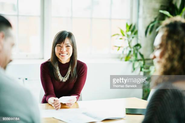 smiling businesswoman in meeting with clients in office conference room - ビジネスウェア ストックフォトと画像