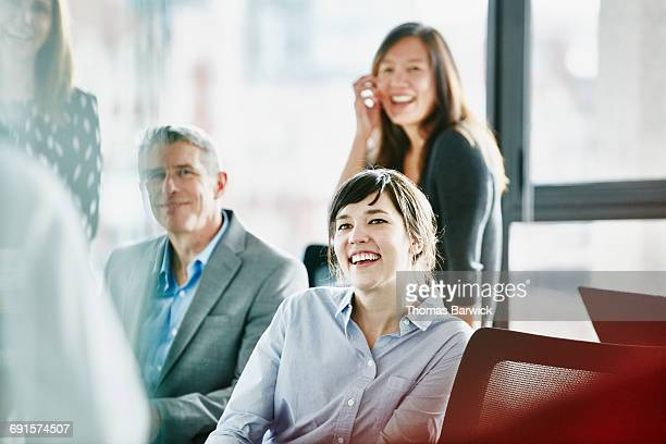 Smiling businesswoman in meeting with coworkers