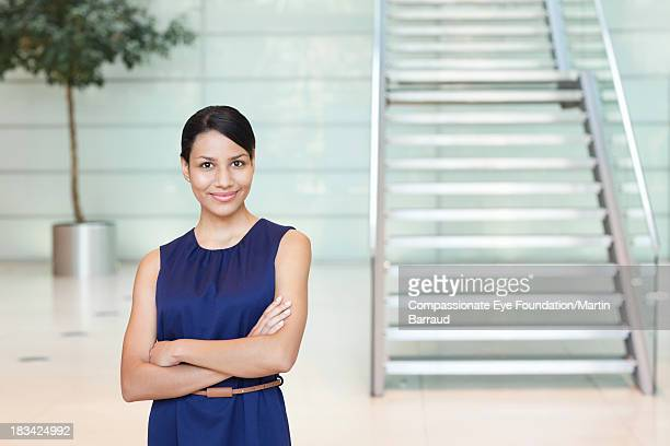 smiling businesswoman in modern lobby - blue dress stock pictures, royalty-free photos & images