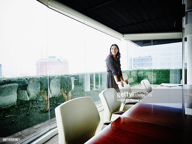 smiling businesswoman in office conference room - leanincollection stock pictures, royalty-free photos & images