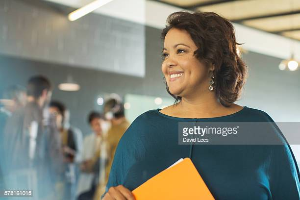 smiling businesswoman in office - onscherpe achtergrond stockfoto's en -beelden