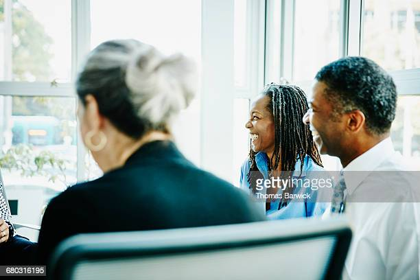 smiling businesswoman in team meeting in office - leanincollection stock pictures, royalty-free photos & images