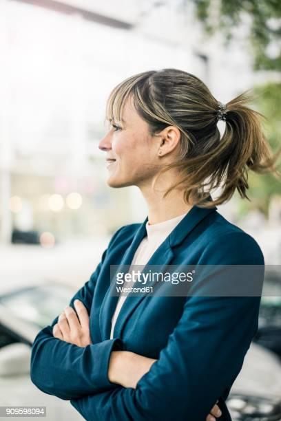 smiling businesswoman in the city - side view stock-fotos und bilder