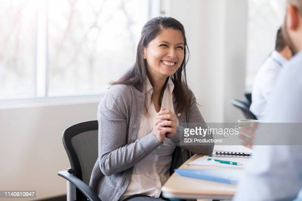 smiling businesswoman interviews job candidate - administrative professionals stock pictures, royalty-free photos & images