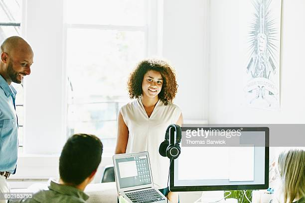 Smiling businesswoman is discussion with coworkers