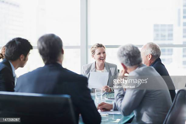 smiling businesswoman leading meeting in conference room - zakenbijeenkomst stockfoto's en -beelden