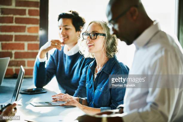 Smiling businesswoman leading meeting with clients and colleagues in coworking space