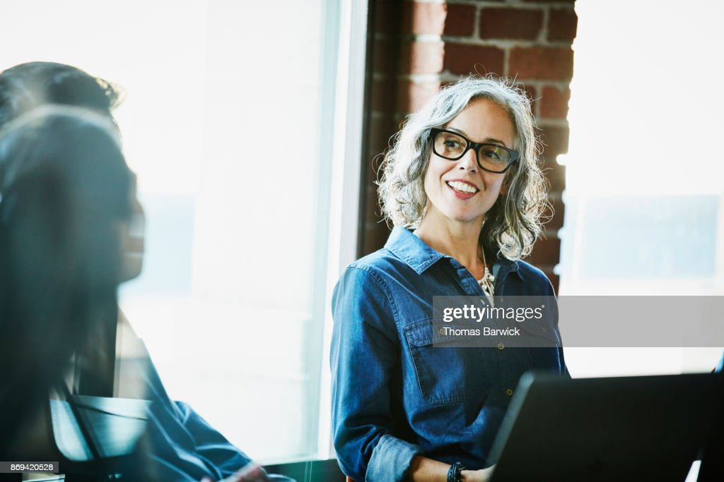 Smiling businesswoman leading meeting with clients in conference room : Stock-Foto