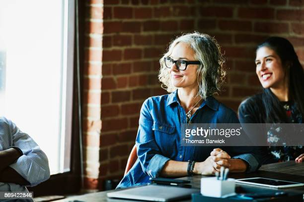 Smiling businesswoman leading meeting with colleagues and clients in office conference room