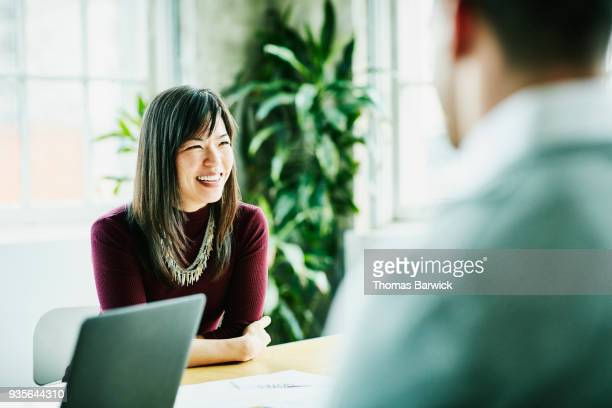 smiling businesswoman leading project meeting in office conference room - advice stock pictures, royalty-free photos & images