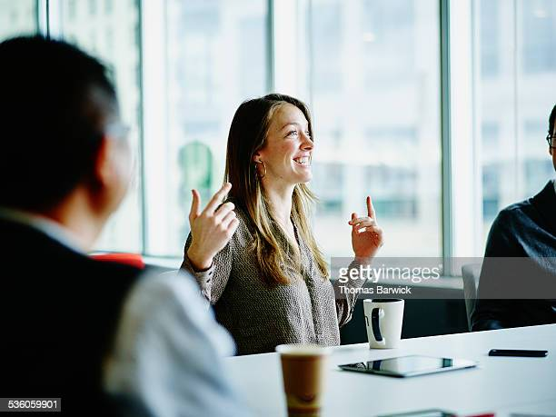 smiling businesswoman leading project meeting - gesturing stock pictures, royalty-free photos & images