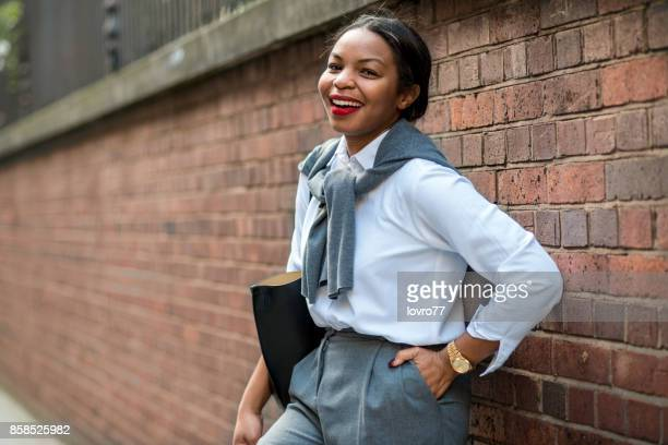 Smiling businesswoman leaning against the wall