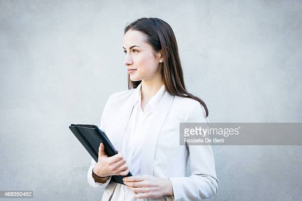 smiling businesswoman leaning against wall portrait - elektronische organiser stockfoto's en -beelden
