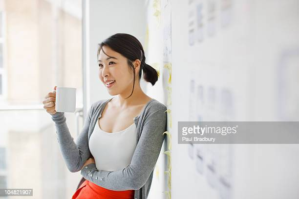 smiling businesswoman leaning against whiteboard and drinking coffee - coffee break stock pictures, royalty-free photos & images