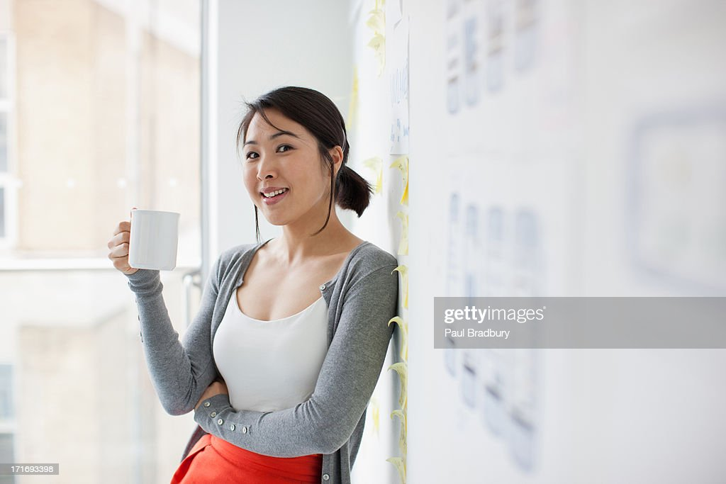 Smiling businesswoman leaning against whiteboard and drinking coffee : Stock Photo
