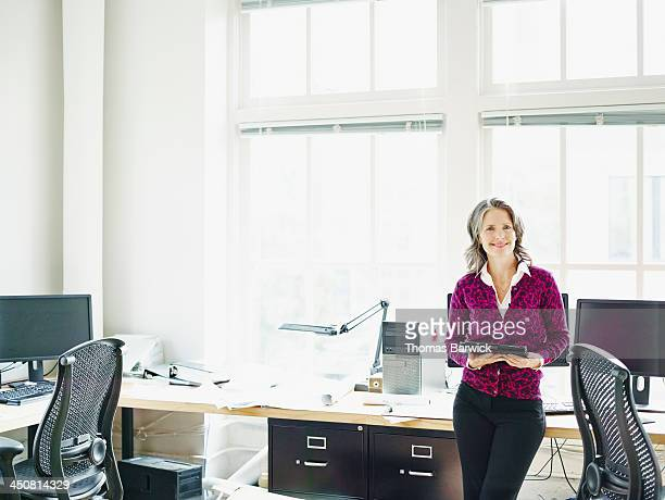 Smiling businesswoman leaning on desk in office