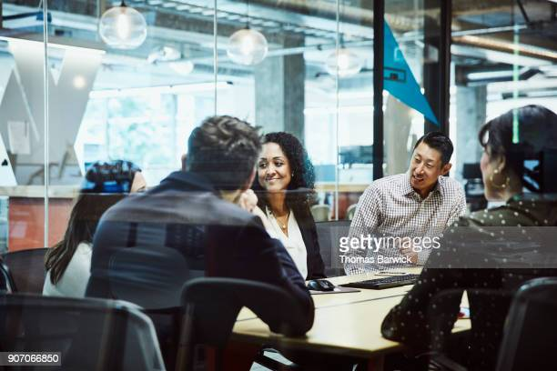 smiling businesswoman listening during client presentation in office conference room - honesty stock pictures, royalty-free photos & images