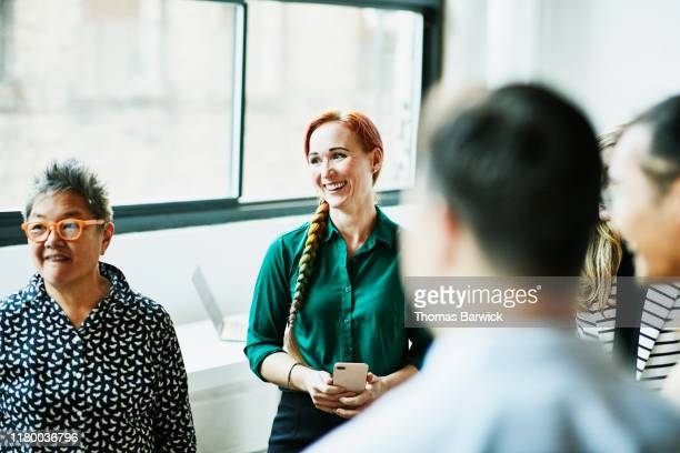 smiling businesswoman listening during team meeting in office - community work stock pictures, royalty-free photos & images