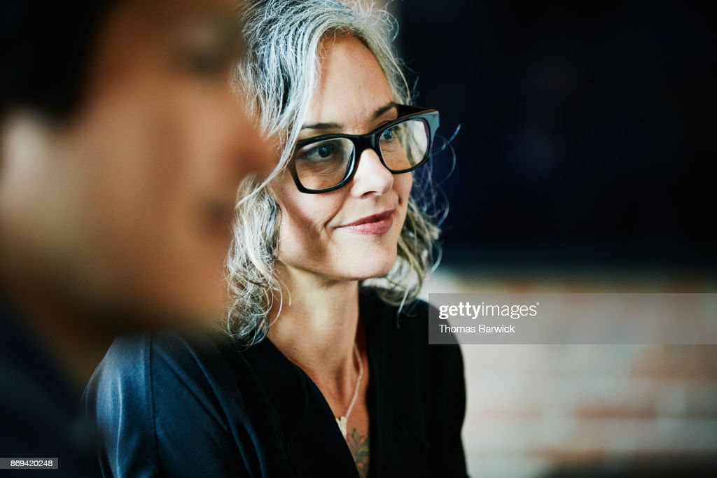 Smiling businesswoman listening during team meeting in office conference room : Stock Photo